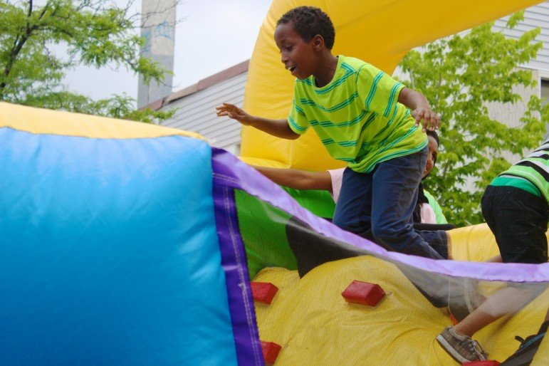 A young boy jumps off a bouncy obstacle course set up by Ka Joog.