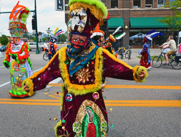 A dancer wearing the traditional Chinelo outfit during East Lake Open Streets