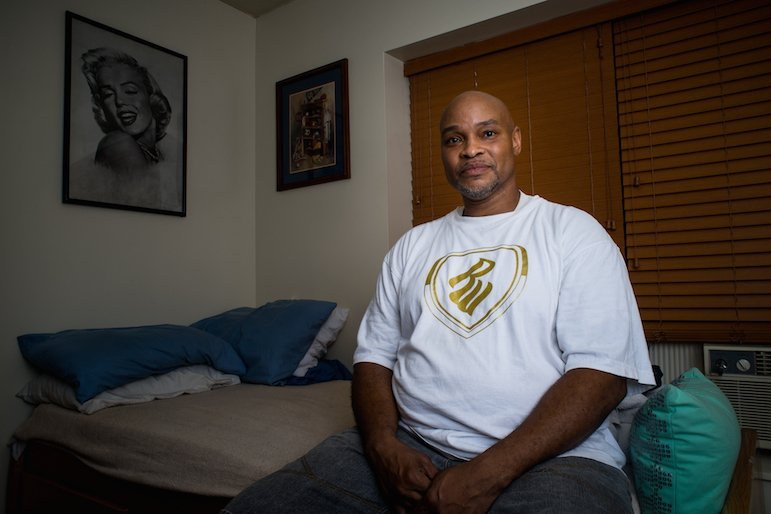 Robert Jackson, 51, sits on the bed in his  studio apartment in south Minneapolis. It took him years to find his own housing after he was released from prison. Photo by Annabelle Marcovici.