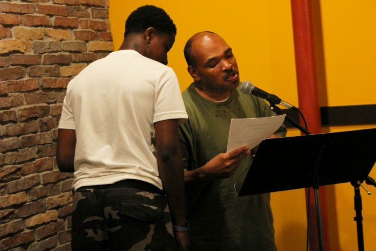 One of Dwayne Davis' supporters whispers the words of the poem in his ear so he can recite it. Photo by Nikki Rykhus.