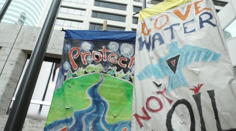 On Sep. 7 banners wave at US Bank Plaza to protest digging for the Dakota Access Pipeline. Photo by Xiaolu Wang.