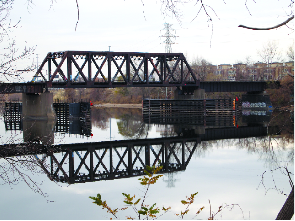This railroad bridge and the Riverview Townhomes comprise one of the views from what is now the parking lot at 1720 Marshall St. NE. Directly across the Mississippi and to the north, heading for the Lowry Avenue Bridge, the views are more industrial. The Minneapolis Park and Recreation Board plans in the short term to store equipment in the former factory building, and later, to turn the parcel into a park. The purchase, $1.37 million, came from $800,000 in grants and the balance from parks' capital funds. (Photos by Margo Ashmore)