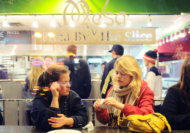 Freshman Madelyn Kraft, right, and friend Eva McCauley enjoy some late-night pizza Saturday at Mesa Pizza. (Photo by Bridget Bennett)