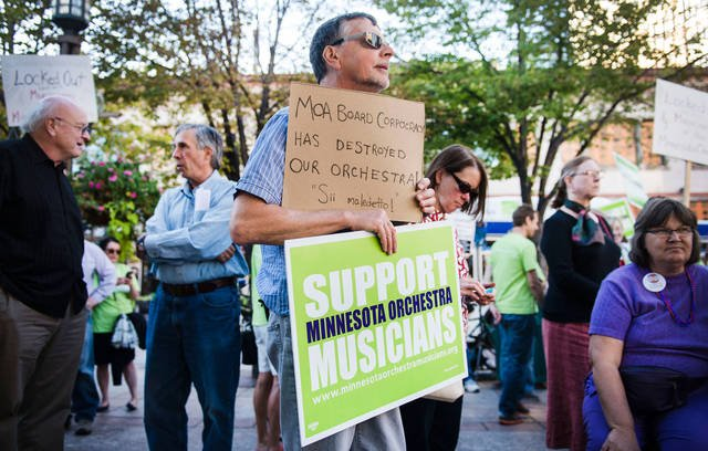 Kurt Rusterholz holds signs in support of Minnesota Orchestra musicians and against the lockout on Tuesday evening outside Orchestra Hall downtown Minneapolis. (Photo by Bridget Bennett)