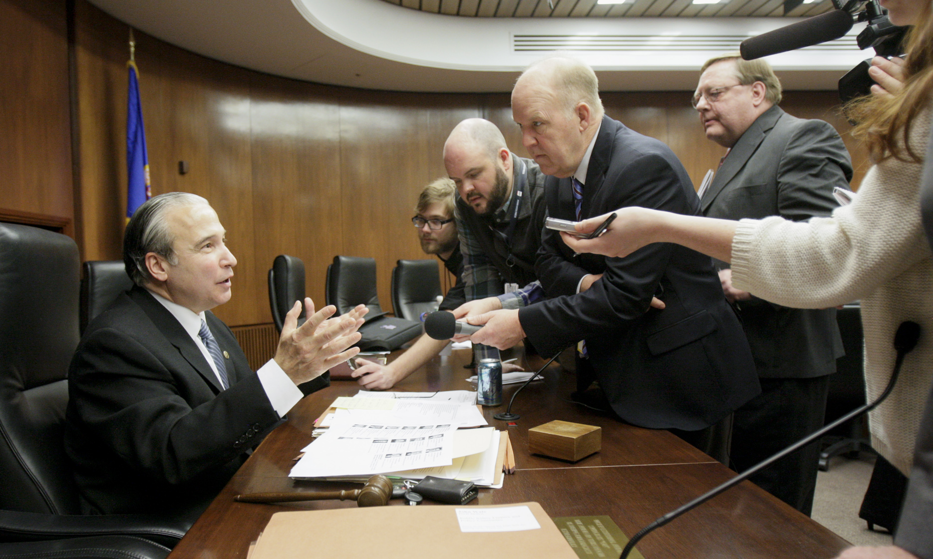 (Pictured above, members of the Capitol press corps gather around House Public Safety Finance and Policy CommitteeChairman Michael Payman, left, after the first of a series of hearings on gun bills.)