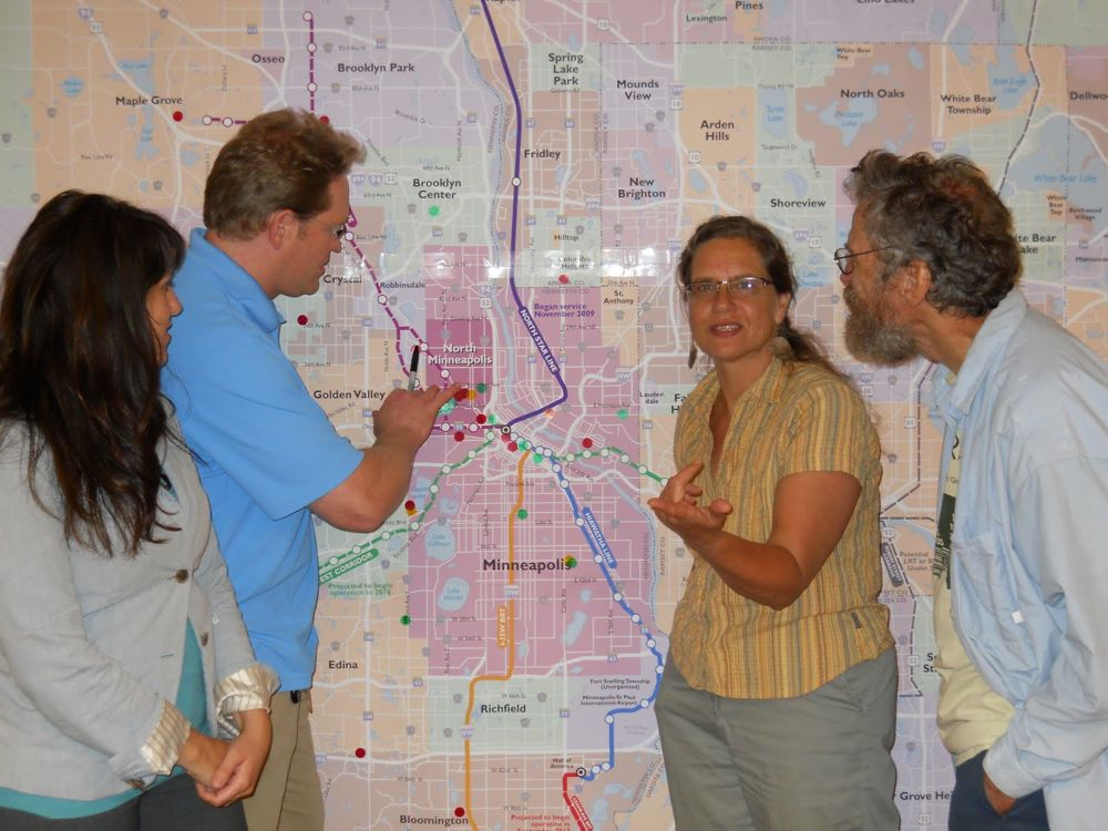 Joan Vanhala (center) with Erin Jerabeck, West Broadway Business & Area Coalition, Geoff Maas, MN Center for Environmental Advocacy, and Fred Olson, North Minneapolis resident, looking at a map of the planned regional transit system.