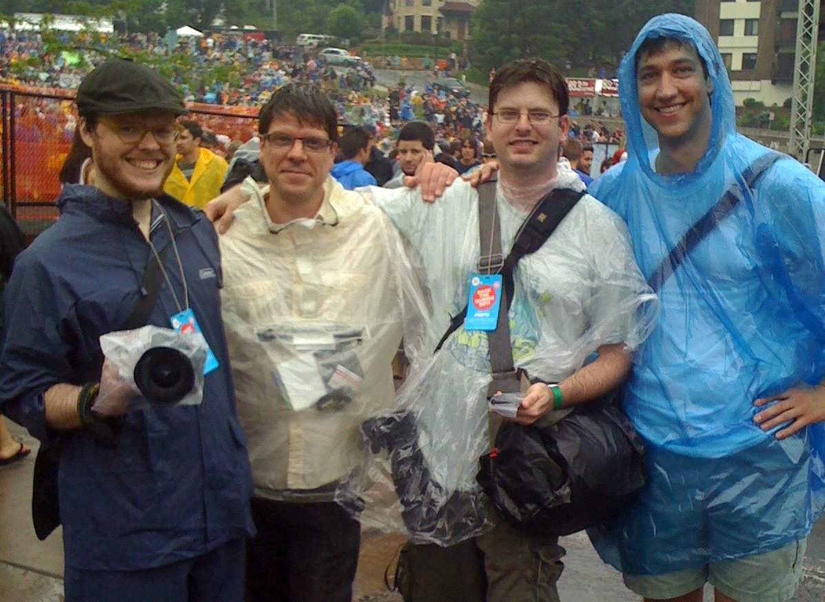 On the job in my blue poncho with fellow journalists (l-r) Ben Clark, David De Young, and Erik Hess at Rock the Garden 2011. Photo by Andrea Swensson.