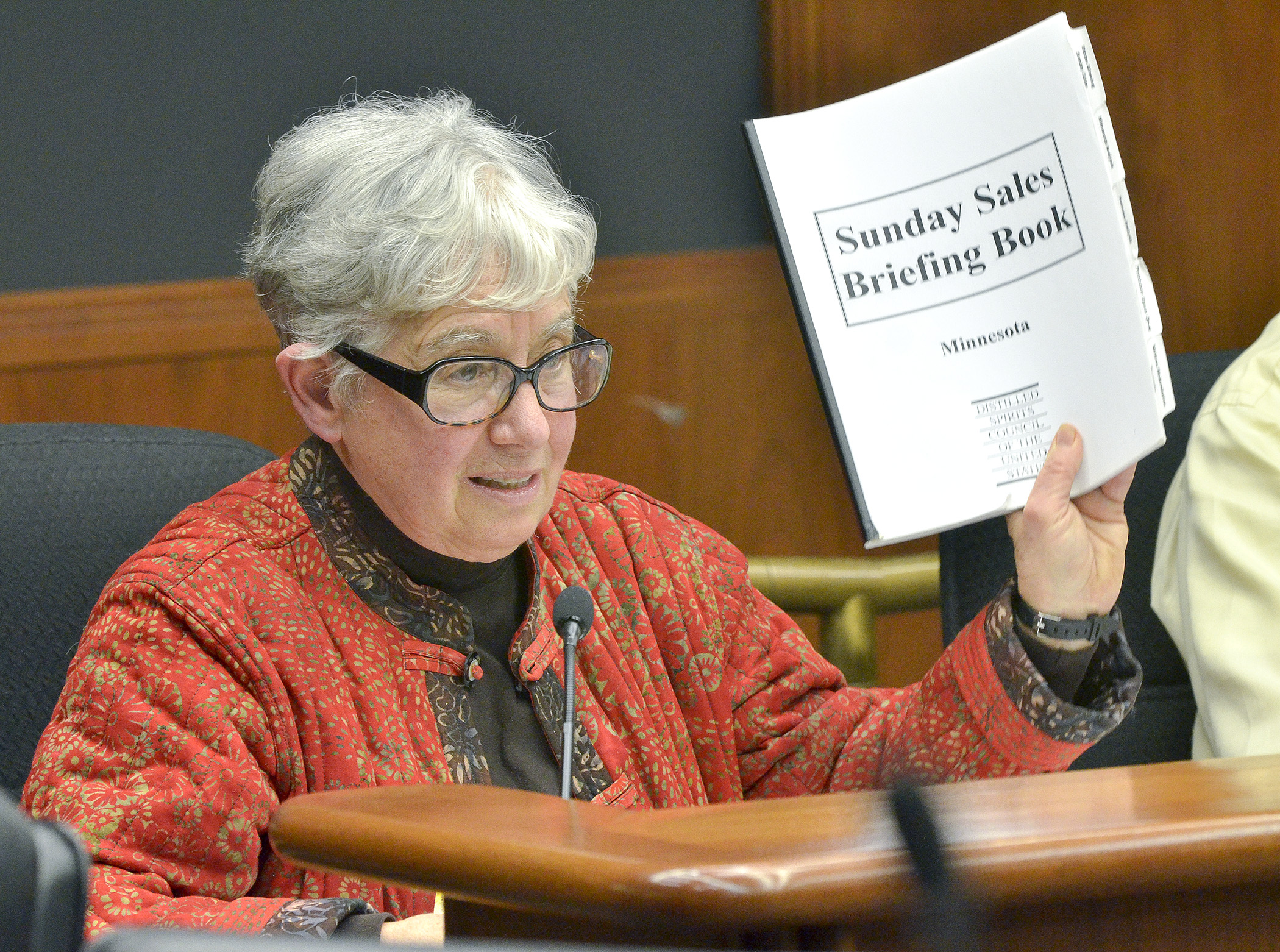 Rep. Phyllis Kahn shows a Sunday Sales Briefing Book to members of the House Commerce and Consumer Protection Finance and Policy Committee Wednesday during an informational hearing on a bill that would repeal Minnesota's Sunday off-sale liquor sales prohibition. (Photos by Andrew VonBank.)