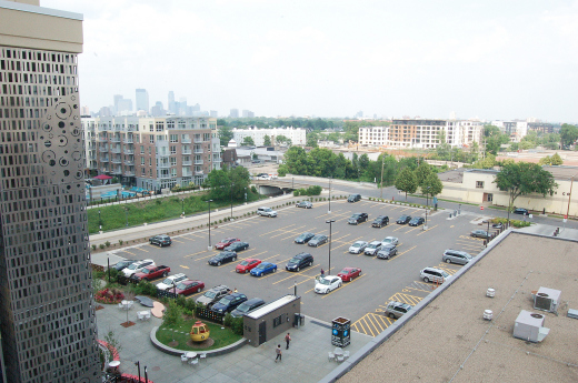 This northeast view shows the location of Phase II (parking lot) from the parking ramp of MoZaic Phase I. The Midtown Greenway is at left center and the Lagoon Theatre is at bottom right. (Photo by Bruce Cochran)