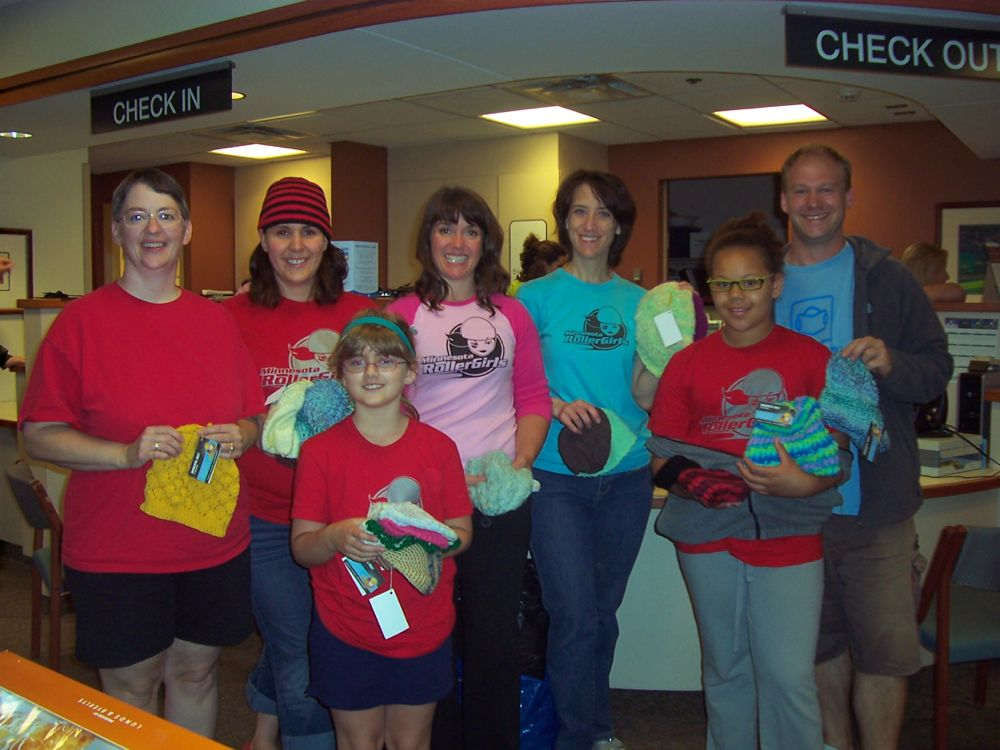 Three skaters and four regular knitters dropping off 250 hats to the University of Minnesota Masonic Cancer Center. From left to right are: Julie Parent, Konceal'N Kari , Shelby Parent, Norah Torious, Skullateral Damage, Alex Leih or Duchess Destruction who skates for NERDY, Pete Leih or Jammit Dim who skates for the TC Terrors. (Photo courtesy of Konceal 'N Kari)