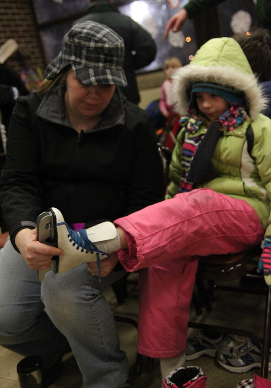A mom helps her daughter put on skates before they head out to the ice.