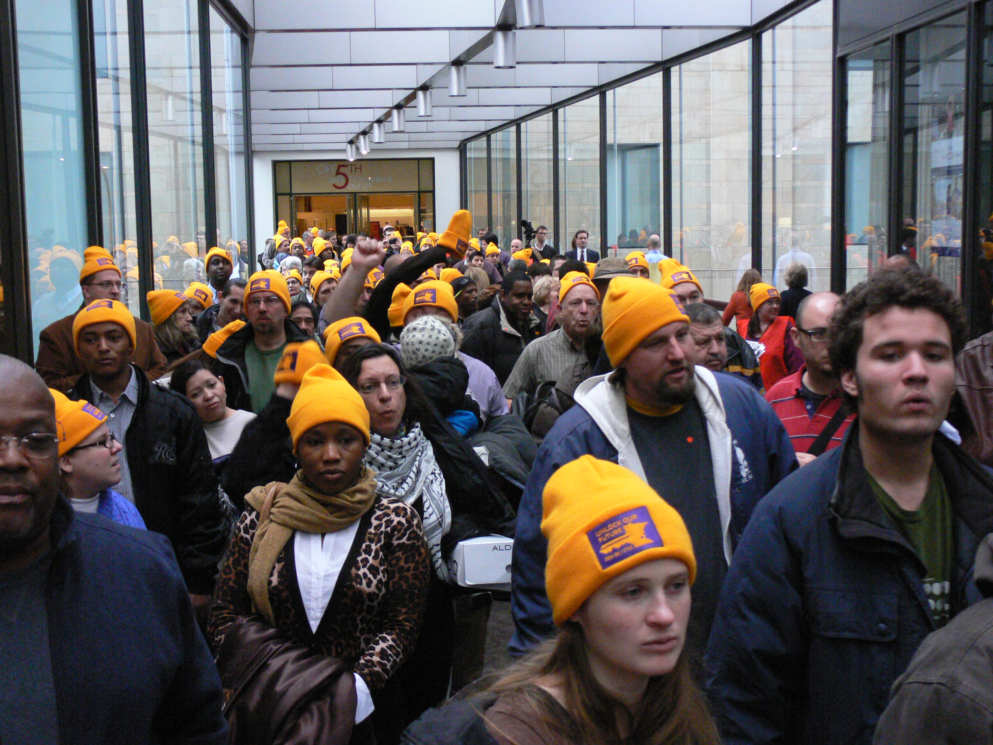 "Hundreds of SEIU Local 26 members and supporters marched through the downtown Minneapolis skyways December 17. Local 26 members work as janitors and security officers for contractors who service downtown Minneapolis buildings. [The ""skyways"" are heated, enclosed bridges which connect much of downtown Minneapolis one floor above street level so people can move about downtown in the winter without going outside--except during the march, when the SEIU folks filled the skyways!] (Photos by Rafael Morataya)"