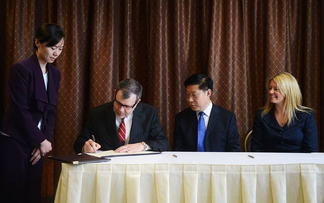 On behalf of the National Center for Food Protection and Defense, President Eric Kaler signs a memorandum of understanding with the Chinese Academy of Inspection and Quarantine. (Photo by Bridget Bennett)
