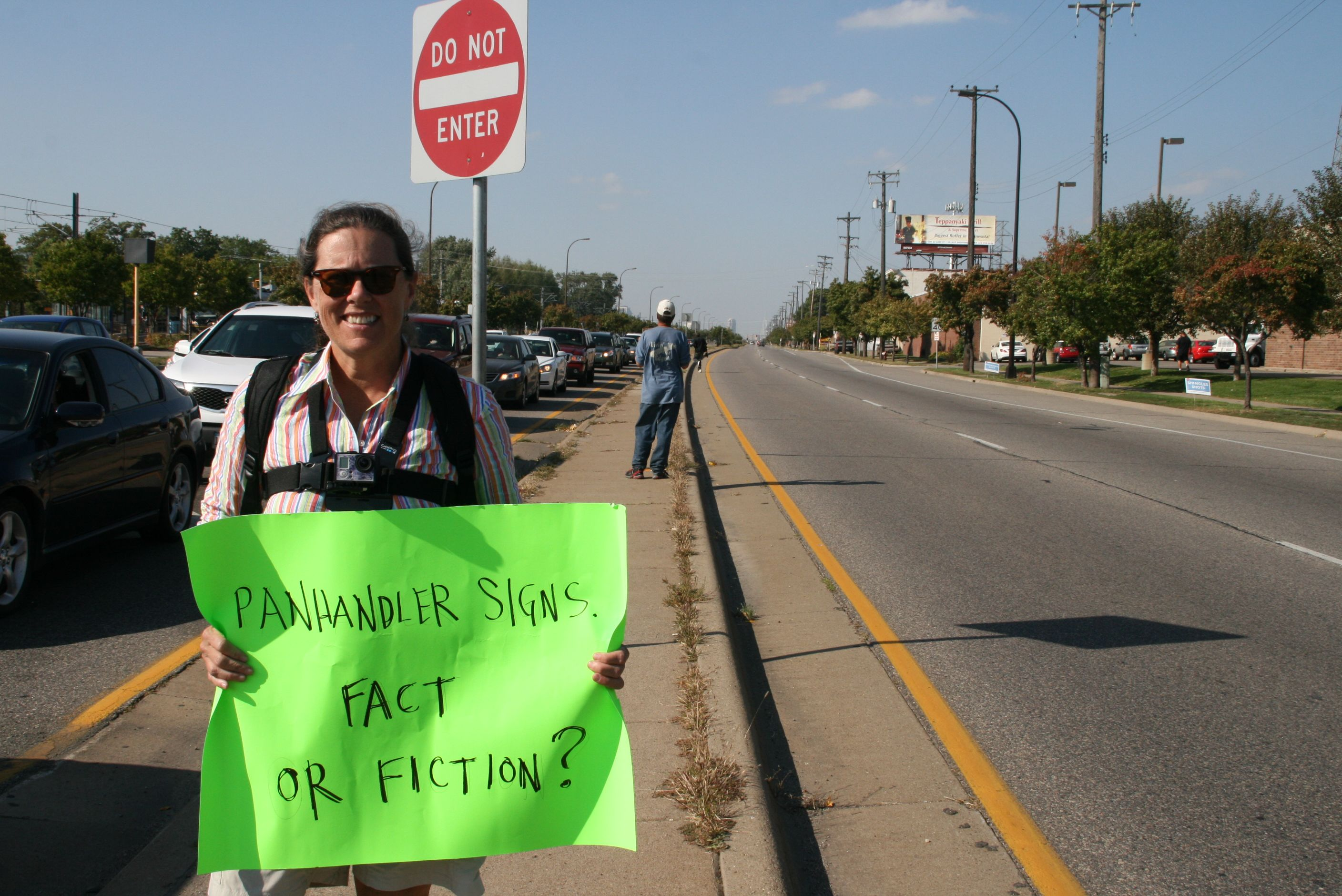 nancy_ford_holds_her_sign_a_few_yards_away_from_a_panhandler._she_has_beenprotesting_10_to_15_hours_a_week_since_early_august
