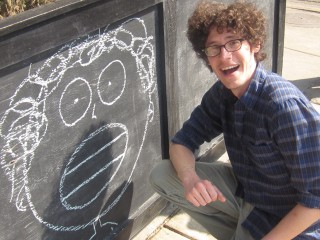 The Nicollet owner, Michael Graca, shows off his drawing skills outside of the shop.  (photo by Paige Elliott)