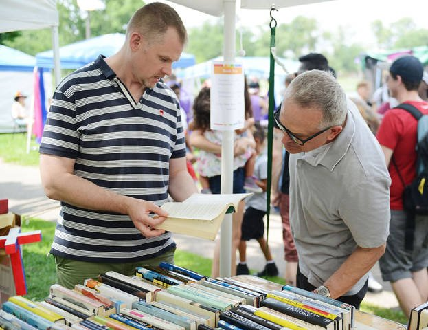 University professor Benjamin Munson and his partner Kevin Burk look through used books at the Twin Cities Pride festival June 28, 2014. Munson and Burk received domestic partnership benefits before they got married last summer. (Photo by Lisa Persson)