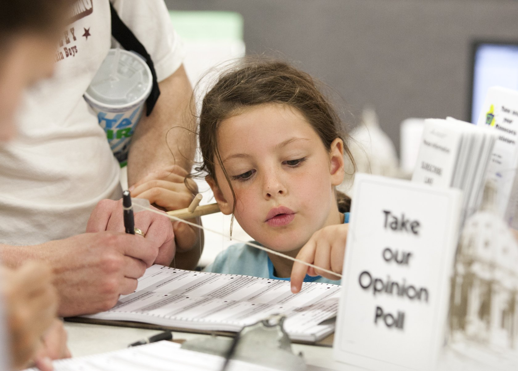 (Photo by Paul Battaglia) A young visitor checks over her dad's answers to the annual House opinion poll at the Minnesota State Fair.