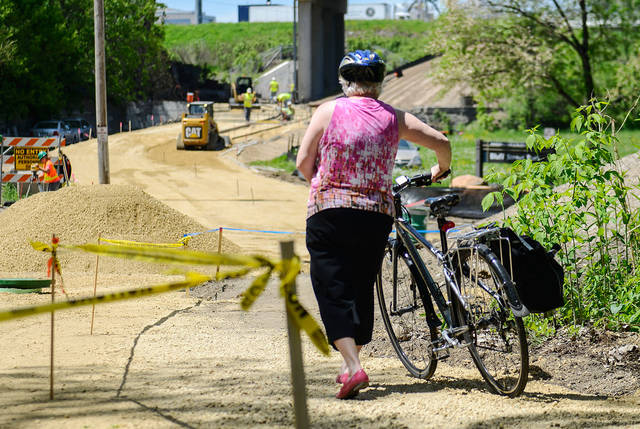 A woman walks her bike past an area where the Bluff Street Bicycle Trail Project is being built. The nearly quarter-mile project will connect the University area to downtown Minneapolis. (Photo by Holly Peterson)