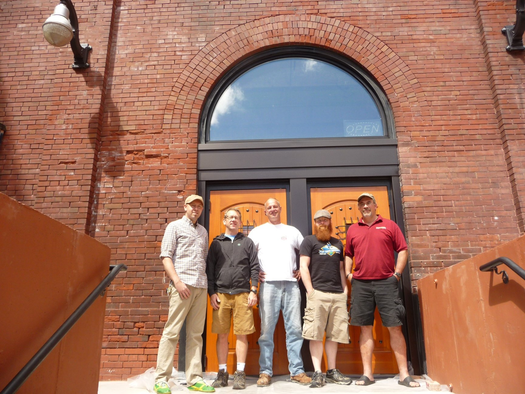 (Photo by Karin DuPaul) Standing in front of the entrance to the Flat Earth Brewing Company are, from left: Lee Egbert and Bob McManus, owners of 11 Wells Distillery; John Warner, owner of Flat Earth; Bob Roepke, Flat Earth Brewer Master; and Franco Claseman, Flat Earth Operations Manager.