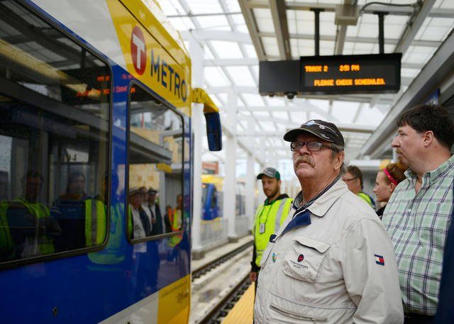 Passengers wait to board the Green Line at Target Field Station on Saturday. Despite the rain, the opening day of the Green Line drew large crowds to ride the new light rail between Minneapolis and St. Paul. (Photo by Chelsea Gortmaker)