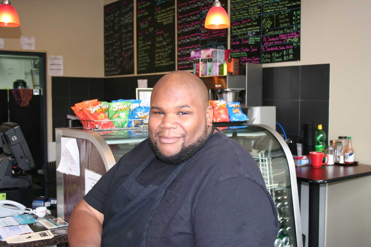 Avenue Eatery owner Sammy Mcdowell pauses from his work to talk about absentee voting.