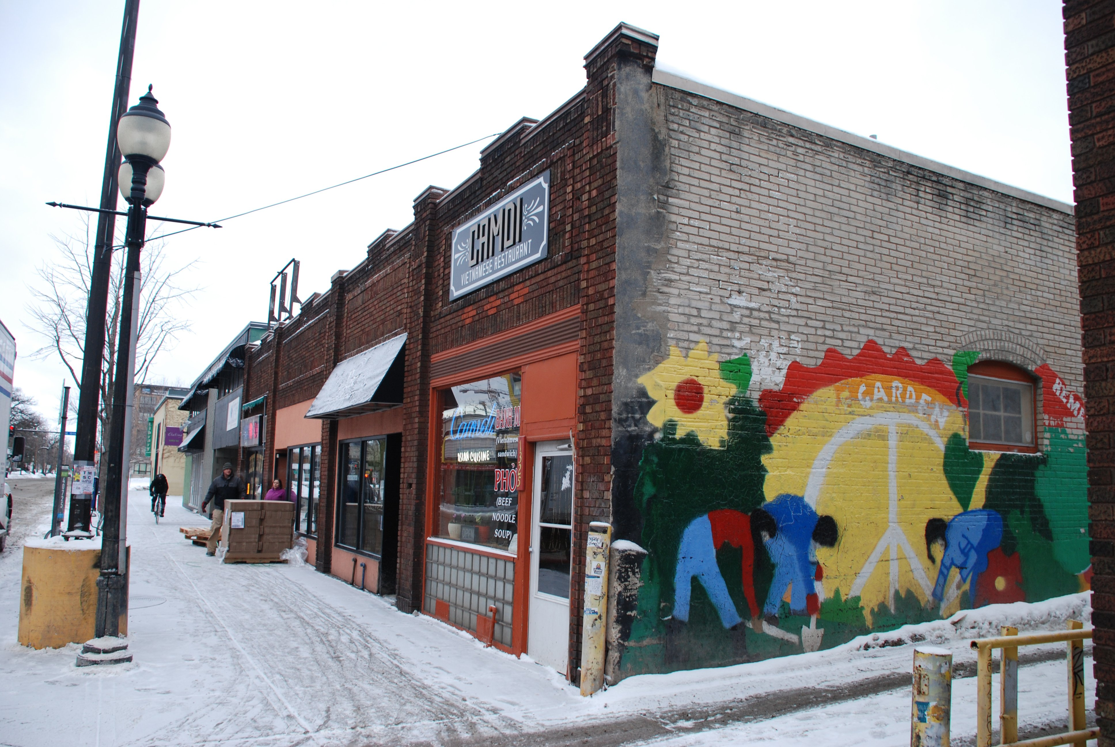 The Minneapolis Historic Preservation Commission unanimously denied Doran Companies' request to demolish this one-story building. The mural celebrates a peace garden planted in 1970 by protestors who prevented the opening of a Red Barn fast-food restaurant in Dinkytown. The Dinkytown Post Office and Hideaway Smoke Shop are on the peace garden/proposed Red Barn site. (Photos by Bill Huntzicker)