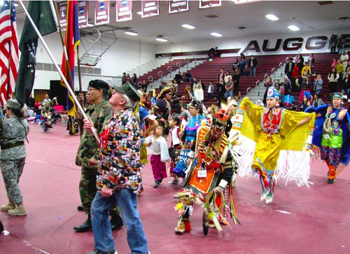 The afternoon Grand Entry at the 7th Annual Augsburg Traditional Powwow in Minneapolis on March 28. Veterans hold a special place in Native American culture, often leading the Color Guard before the dancers. (Photo by Deanna StandingCloud)
