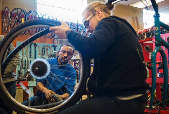Earn-a-Bike student Wondey Geta observes as mechanic Ben Swanson demonstrates how to remove a bike tube at SPOKES on Saturday morning. Photo by James Healy, via the Minnesota Daily.