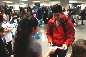 Miles Thompson signs autographs for the youth in the Twin Cities Native American Lacrosse Club, who came to welcome him as he arrived in Minneapolis on Jan. 2. (Photo by Alfred Walking Bull)