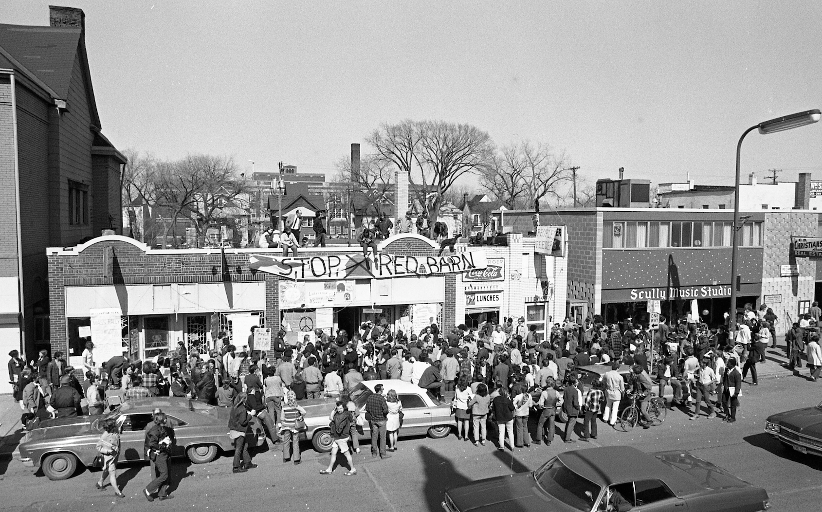 Protesters gathered in and around vacated buildings for a month in 1970 to prevent their demolition for the construction of a fast-food restaurant. Over the roof, you can see Marshall High School in the distant background a block away and some former Victorian homes that had been converted to businesses. Photo by and Copyright Cheryl Walsh Bellville.