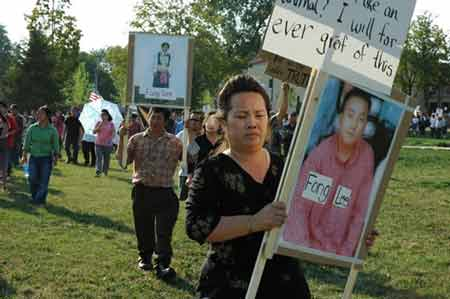 Nou Kai Lee and Youa Vang Lee, the parents of Fong Lee, at Monday's vigil.