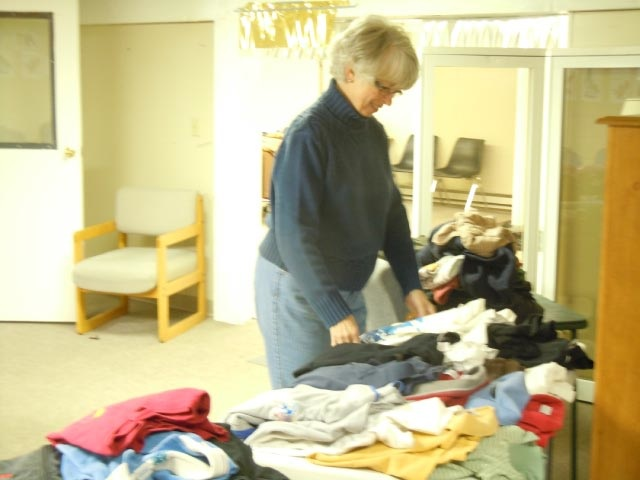 A volunteer folds clothes at FOCUS.