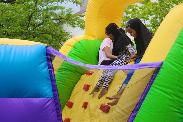 Two young girls slide down the bouncy house.