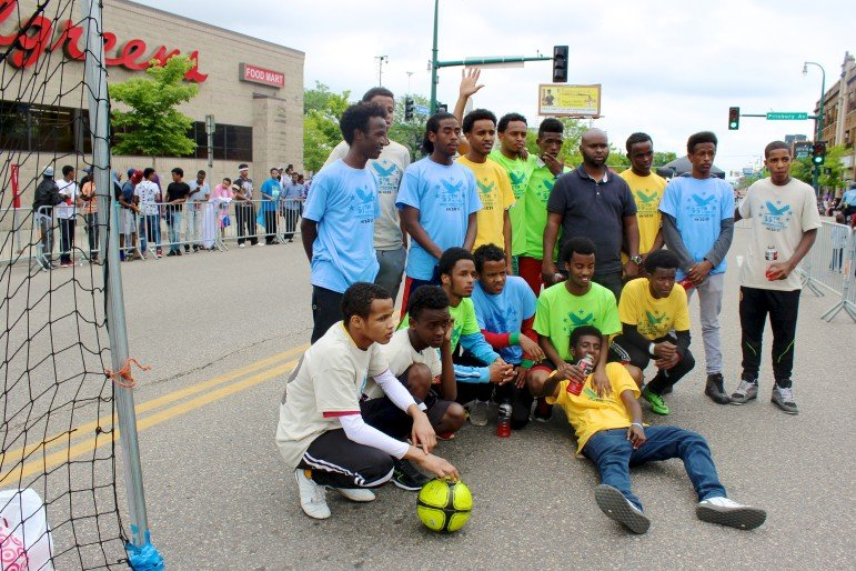 Soccer teams pose after they finished a friendly game.