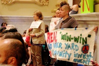 """An opponent held a sign that read, """"real 'win-win' is no water yard and community investment."""" Photo by Kayla Steinberg"""