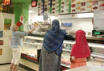 Photo- Customer Blanca Grandi talks to one the store's butcher in Spanish.