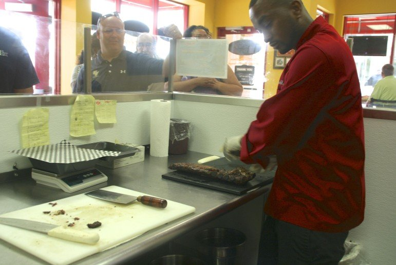 Kenneth Wortham slices up barbeque ribs for a long line of luncheon customers.