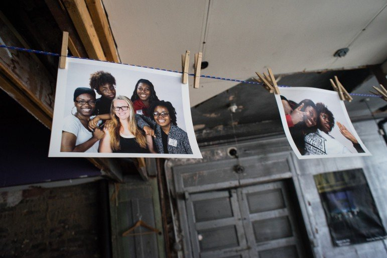 Photos of Victoria Theater youth fellows hang from a clothesline inside the new theater. Photo by Annabelle Marcovici