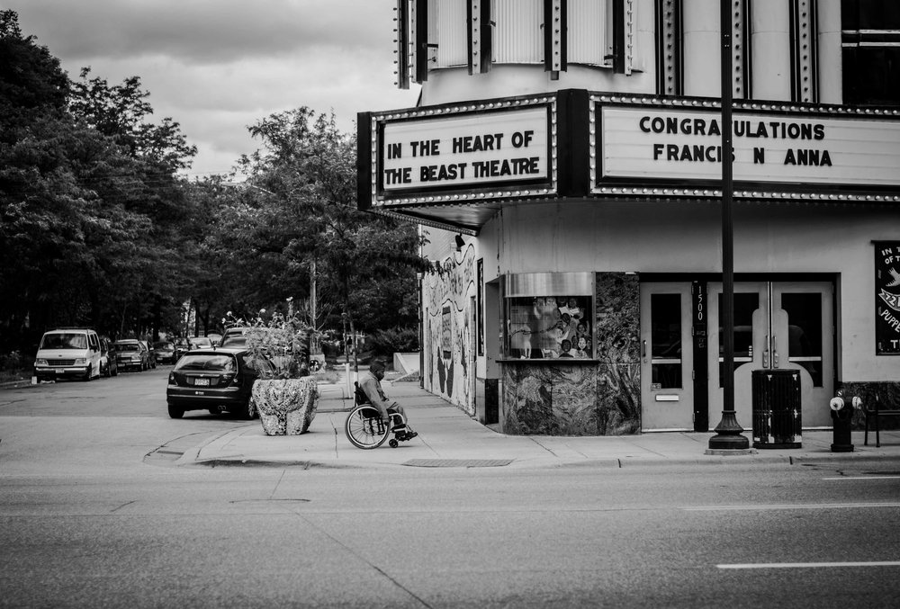 Man in wheelchair, Lake Street Minneapolis. Photo by emerging artist Netsanet Negussie, 2015.