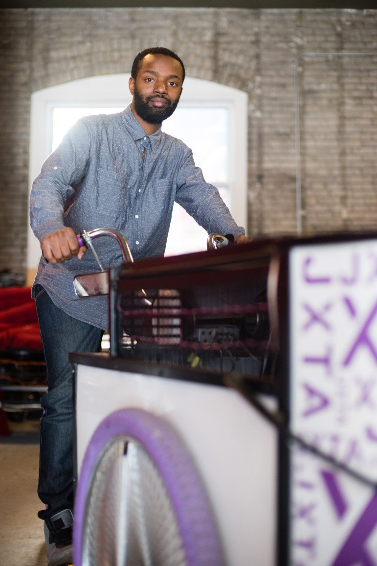 Brown demonstrates the custom cycle he built for Juxtaposition Arts. Photo by Annabelle Marcovici.